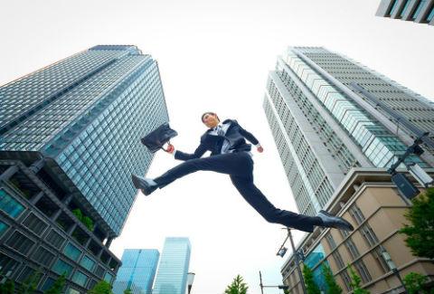 ビルの間を飛ぶビジネスマン